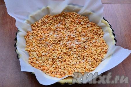 На тесто поместить пергамент и насыпать горох или фасоль.