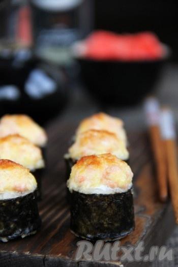 Запекать вкусные роллы в разогретой духовке при температуре 200 градусов при верхнем нагреве, примерно, 10 минут. Поверхность шапочки должна покрыться красивой золотистой корочкой. Подать приготовленные запечённые роллы в горячем виде с соевым соусом и имбирём.