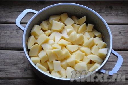 Поверх обжаренных овощей и колбасы выложить кубики картофеля.