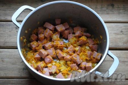 В кастрюлю с толстым дном или казанок влить растительное масло и хорошо его разогреть. Обжарить лук с морковкой на среднем огне до золотистого цвета (около 5 минут), периодически помешивая. Затем добавить колбасу и обжарить всё вместе ещё 2-3 минуты.