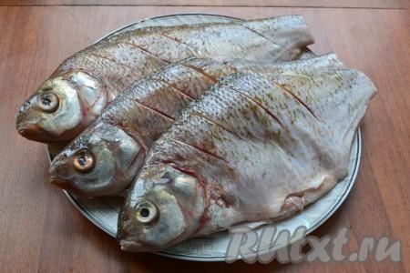 Рыбу очистить, удалить внутренности, плавники и хвост, хорошо вымыть. Ближе к спинке, с двух сторон, сделать по 5-6 надрезов.