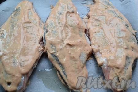 Противень застелить пергаментом и смазать растительным маслом. Каждую рыбку щедро обмазать с двух сторон подготовленным соусом и выложить на застеленный и смазанный маслом противень.