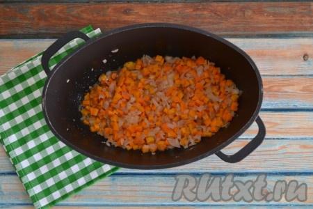 Очищенные лук и морковь нарезать мелкими кубиками. Разогреть казан или сковороду на огне, влить растительное масло, а через минуту выложить морковку с луком и обжарить в течение 2-3 минут на среднем огне, иногда помешивая.