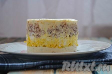 Дальше выложить слой из печени трески, а затем снова идёт слой из сыра и чеснока. Яичный желток, который мы оставляли для украшения, натереть на мелкой теркой и посыпать им верх салата. Отправить салат в холодильник минимум на 30 минут.