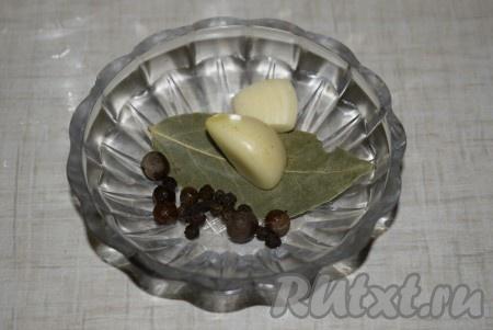 В каждую банку положить чеснок, нарезанный на пластины, и добавить перец горошком, душистый перец, лавровый лист и гвоздику.