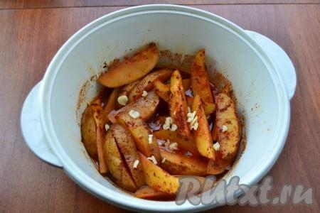 Поместить форму с картошкой в микроволновку, готовить 10 минут при полной мощности (у меня - 750 Ватт). Готовый горячий картофель по-деревенски смешать с измельченным чесноком.