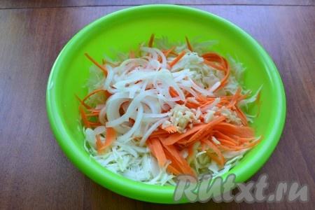 Очищенный лук, нарезанный тонкими полукольцами, и измельченный очищенный чеснок выложить к капусте с морковью и немного подавить руками.