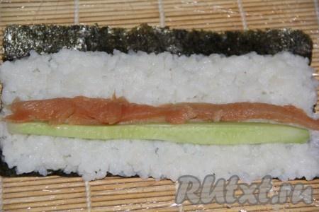 Красную рыбу нарезать на длинные полоски. Вымытый огурец нарезать на длинные брусочки. Выложить на рис брусочек огурца, рядом сделать полоску из кусочков рыбы.
