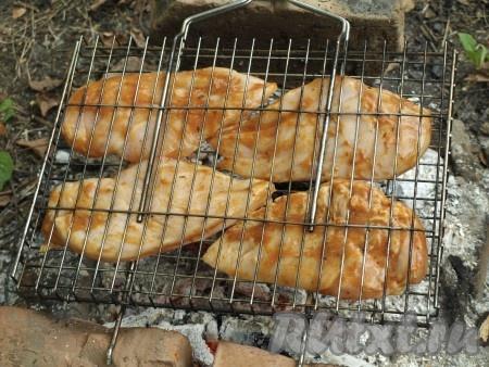 Разжигаем мангал и ждём, когда прогорят дрова до седых углей. Решётку с куриными грудками выкладываем на мангал.