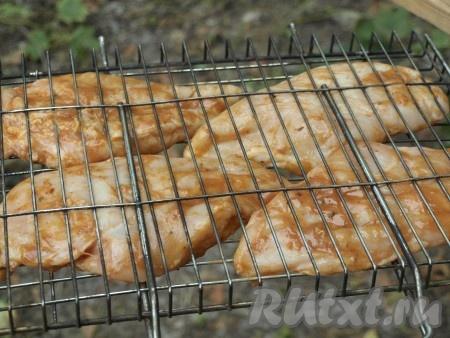 Куриные грудки выкладываем на решётку, немного солим с двух сторон.