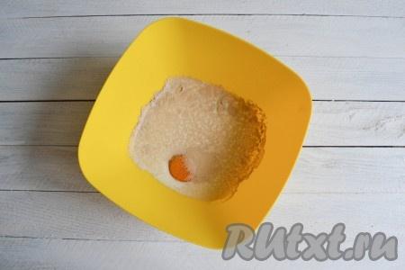 В глубокую миску влить молоко, всыпать дрожжи и добавить яйцо.