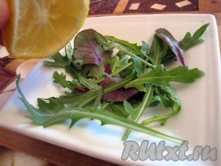 Подавать салат эффектнее порционно - 4-5 порций. На тарелку выложить салатные  травки и сбрызнуть их лимонным соком.