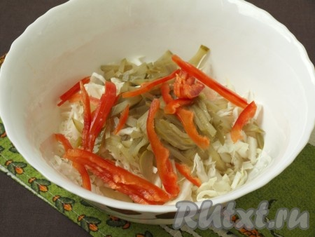 Тонкой соломкой нарезать маринованный огурец и свежий болгарский перец, очищенный от семян. Сложить в миску капусту, добавить болгарский перец с огурцом.