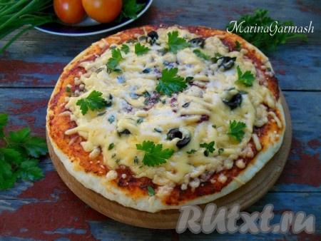 Выпекайте пиццу в предварительно разогретой духовке при температуре 180 градусов в течение 10-12 минут. Вынув горячую пиццу из духовки, я всегда посыпаю ее тертым сыром поверх начинки. Когда пицца будет готова, переложите ее на доску, дайте немного остыть, разрежьте на куски и подавайте.