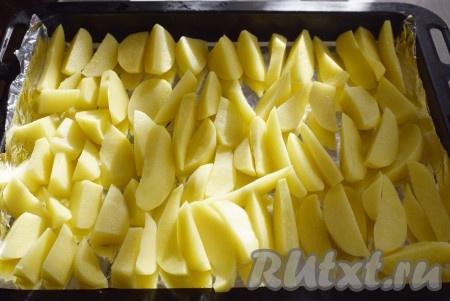 Форму или противень для запекания застелить фольгой или пергаментом. Нарезать картофель на крупные дольки.На фольгу выложить картофель и присыпать специями и солью.