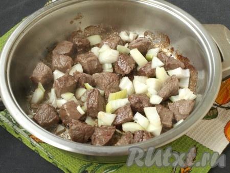 Разогреть в сковороде подсолнечное масло, выложить кусочки мяса и обжарить на среднем огне до румяной корочки со всех сторон. Затем выложить к мясу нарезанный кубиками очищенный лук и обжарить, помешивая, до прозрачности лука.