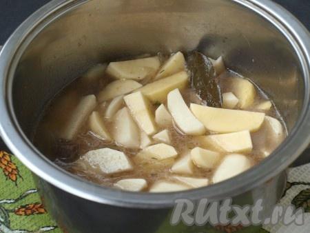 Картофель выложить к мясу, если мало воды - добавить (вода должна покрыть картошку на 2/3). Также добавить лавровый лист, приправы (здесь вы вольны в выборе и можете добавить любимые приправы, например, прованские травы, смесь трав для картофеля или отдельно взятые травы), довести до кипения и уменьшить огонь. Готовить картофель 10 минут под крышкой.