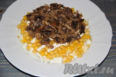 Грибы после жарки остудить. Затем на слой кукурузы выложить остывшие шампиньоны и слегка посолить.