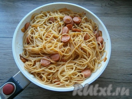 Qaynatilgan spagetti sosiska bilan sosga soling, aralashtiring.