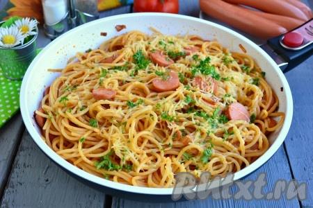 Kolbasa bilan pishirilgan mazali spagetti, issiq shaklda stolga xizmat qiling.