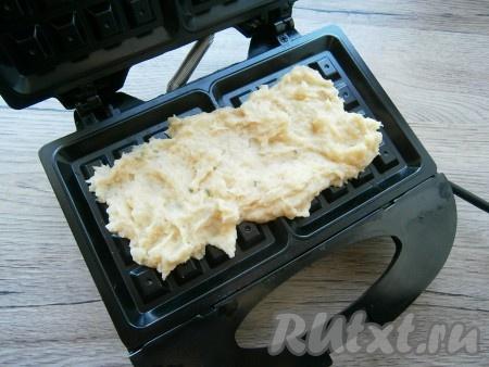 Электровафельницу хорошо разогреть. Выкладывать в вафельницу по 2-3 столовые ложки картофельной массы, немного размазывая ее.