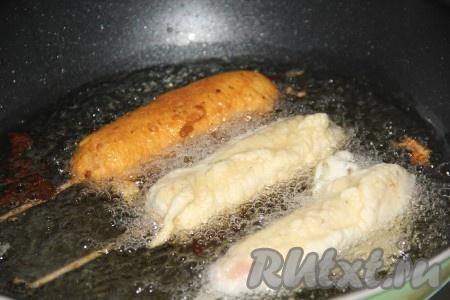 Растительное масло хорошо разогреть. Для жарки корн-догов я использовала глубокую сковороду. Выложить сосиски в тесте в разогретое масло (во фритюр).