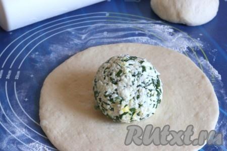 Разделить тесто на 2 части. На столе, присыпанном мукой, одну часть теста раскатать в лепёшку толщиной 8-9 мм. Начинку из адыгейского сыра скатать в шар и поместить в центр лепешки.