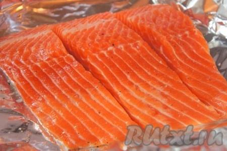 Филе сёмги разрезать на порционные кусочки, но !) не прорезая кожу. Фольгу расстелить в форме для запекания, выложить рыбу на фольгу, посолить, добавить перец.