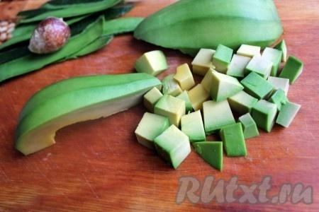 Пока куриное мясо маринуется, очистить авокадо, вынуть косточку и нарезать его кубиками.