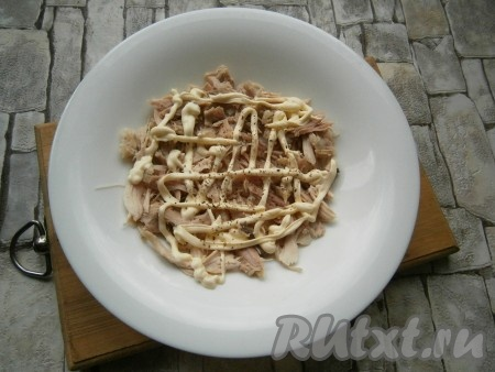 На тарелку выложить 2/3 части отварной курицы, порванной руками на волокна, нанести сеточку из майонеза, немного поперчить.
