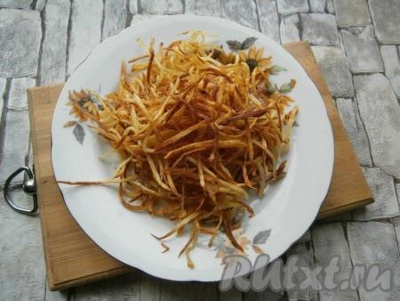 Обжарить картофель частями на растительном масле до золотистого цвета на среднем огне, перемешивая его (много в сковороду не кладите, нужно добиться более-менее равномерного обжаривания). Картофель солить не нужно! Жареную соломку из картофеля выкладывать на бумажное полотенце для удаления лишнего жира. Дать картофелю остыть.