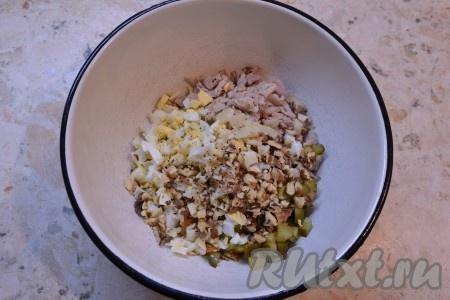 Нарезанные огурчики, яйца и мясо соединить в миске, добавить измельченные грецкие орехи и мелко нарезанный чеснок.
