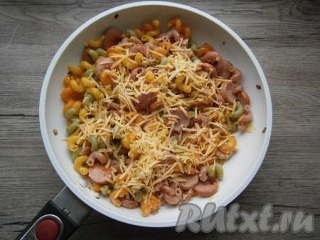Макароны с сосисками и луком посолить, поперчить, перемешать. Далее влить желтковую смесь, добавить половину натертого сыра, быстро все перемешать. Прогреть блюдо минуты 3-4 под крышкой на слабом огне.