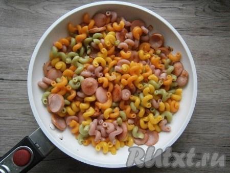 Сосиски обжарить вместе с луком, помешивая, в течение нескольких минут, после чего добавить к ним макароны, перемешать.
