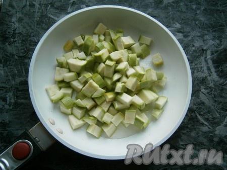 Нарезать кабачки кубиками, размер которых около 1 см, выложить в сковороду, влить растительное масло.