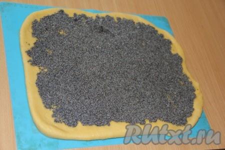 Тесто разделить на 2 равные части. Раскатать каждую часть в пласт толщиной, примерно, 0,5 см. Выложить маковую начинку на тесто, равномерно распределяя её по поверхности каждого пласта теста.