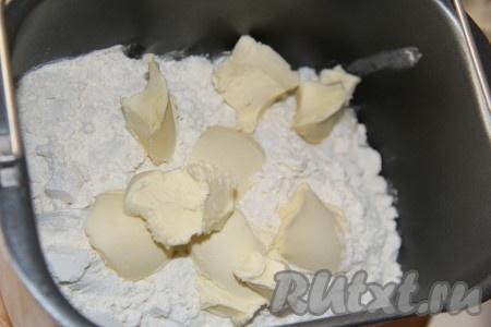 Затем всыпать муку, а сверху выложить кусочки размягченного сливочного масла, закрыть крышку хлебопечки. Для того чтобы масло было размягченным, его нужно заранее вынуть из холодильника.