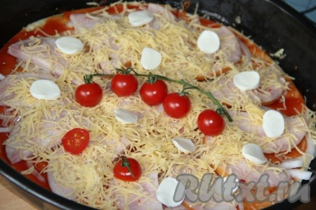 Посыпать пиццу тёртым сыром и выложить помидоры черри для украшения. Затем выложить моцареллу, я разрезала шарики на две части (можно натереть на тёрке). Выпекать пиццу с начинкой из ветчины и сыра 10-12 минут при температуре 220 градусов. Аналогично сформировать и испечь пиццу из второй части тесте.