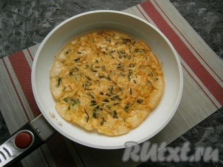 Сковороду накрыть крышкой, огонь убавить до минимального и жарить лепёшку около 3-5 минут. Сверху тесто не должно остаться жидким. Затем картофельную лепёшку перевернуть.