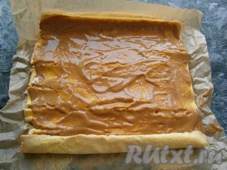 Остывший бисквитный рулет аккуратно развернуть, пергамент снять. Смазать бисквит варёной сгущёнкой, смешанной с маслом и сметаной.