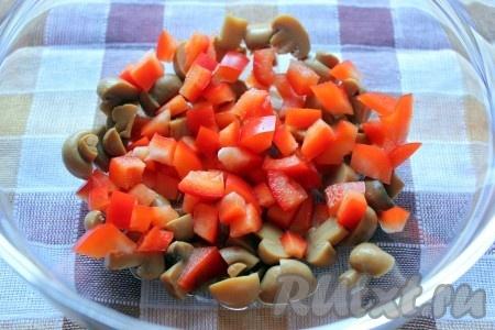Маринованные шампиньоны порезать на половинки или четвертинки, в зависимости от их размера. Красный болгарский перец нарезать кубиками.