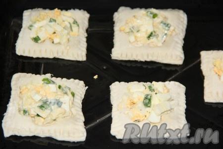 Положить начинку из зелёного лука, яиц и сыра в углубления слоек. Я начинку выкладывала с горкой. Выпекать пирожки из слоёного теста в разогретой духовке, примерно, 25 минут при температуре 180 градусов.