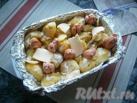 Через 30 минут картофель достать из духовки, вставить половинки сосисок (надрезами кверху) между клубнями картофеля и разложить кусочки сливочного масла.