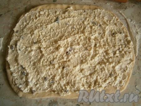 Хорошенько перемешать творожную массу, чтобы не осталось комочков творога и масла. Когда тесто увеличится в объёме раза в 2, обмять его. Посыпать стол 30 граммами муки. Разделить тесто на 2 части. Каждую часть теста раскатать в прямоугольный пласт толщиной около 0,5 см. Смазать раскатанное тесто творожной начинкой.