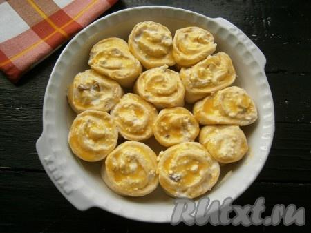 Смазать булочки оставленным желтком.
