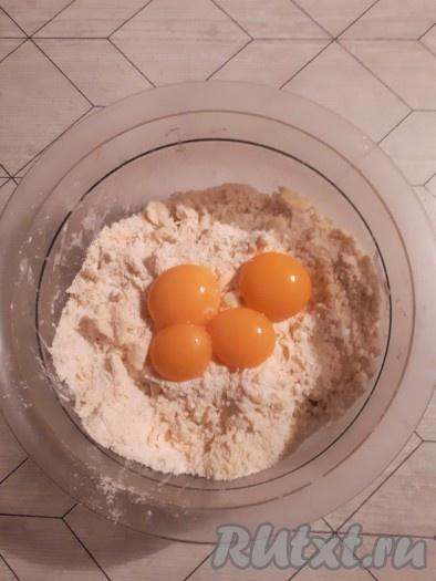 Разделить яйца на белки и желтки. Белки отправить в холодильник. Желтки добавить к крошке и быстро замесить тесто.