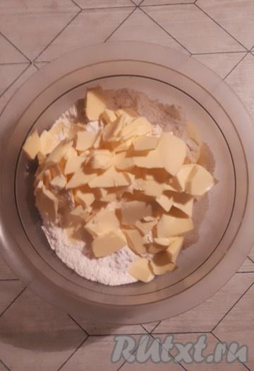Просеять в миску муку с разрыхлителем и сахарной пудрой, затем добавить нарезанное на кусочки сливочное масло и перетереть получившуюся массу в крошку.