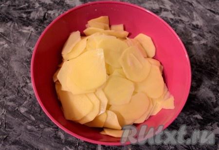Картофель очистить и нарезать тонкими слайсами. Сделать это можно овощечисткой (или с помощью шинковки для капусты).