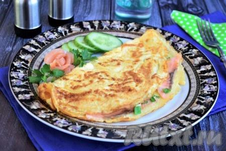 Аккуратно выложить вкуснейший и нежнейший омлет с сёмгой на тарелку, украсить свежими овощами, зеленью и сразу подать к столу.