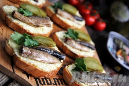 Вкусные, аппетитные бутерброды, приготовленные со шпротами и солёным огурцом, украсив веточкой зелени, подать к столу. Эта простая закуска станет прекрасным дополнением и к праздничному, и к повседневному столу.